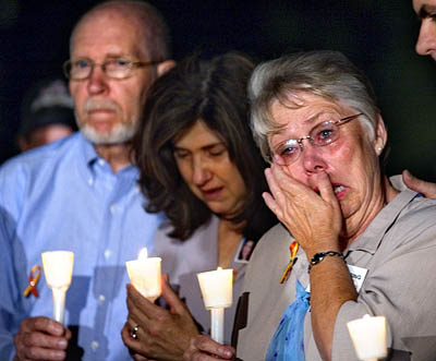 A candle light vigil is held for missing person Lori Hacking. Thelma Soares, right, displays her emotions flanked by Mark Hacking's parents Janet (middle) and Douglas Hacking (right).