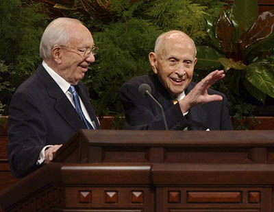 Gordon B. Hinckley, president of The Church of Jesus Christ of Latter-day Saints, invites Elder David B. Haight up to the podium to wave to the crowd before excusing him from the meeting of a Saturday morning session of LDS General Conference last October.