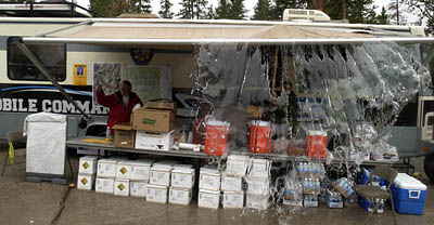 Accumulated rain is poured out of the awning of the mobile command center near Mirror Lake. Weather today in the Uintahs hampered the search for 12 year old Garrett Bardsley who has been lost in the mountains since Friday.