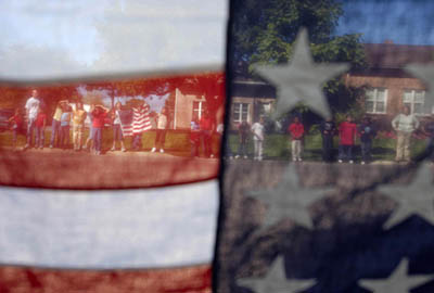 Seen through an American flag, students from the Blanding Elementary School lined the street (100 West) as the funeral procession of Marine Quinn Keith, killed in Iraq, went through his hometown of Blanding, Utah, Wednesday.