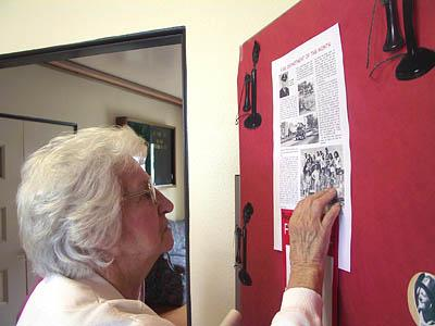 Alva Batty, 83, looks for her face in a group photograph of Kanarraville's all-women volunteer firefighting force of the 1960s. The picture was part of an exhibit in Kanarraville on Saturday.
