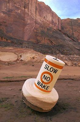 A warning buoy beached due to the low water level in Forgotten Canyon on Lake Powell in 2003. A wet autumn and winter and what looks to be a moist spring could pull the lake level up 50 feet.