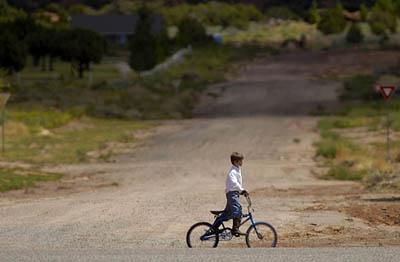 A boy rides his bike in Colorado City, Ariz. Hildale, Utah and Colorado City are home to a community of about 10,000 members of the Fundamentalist Church of Jesus Christ of Latter Day Saints (FLDS).