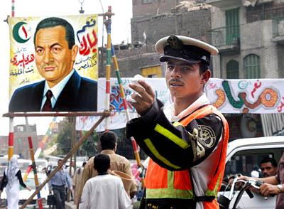 An Egyptian traffic soldier works an intersection Wednesday near one of many posters of President Hosni Mubarak. The incumbent is expected to win today's vote easily after an unprecedented campaign.