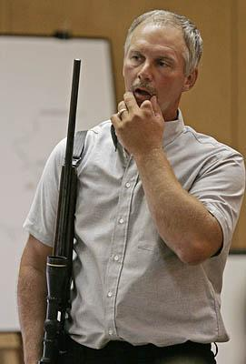 Terry Willers holds a rifle while testifying about the shootings last year in Wisconsin.