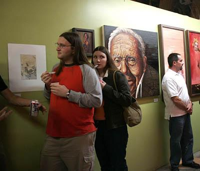 Jeremy Mathews, left, chats with another gallery visitor as Jessica Mathews, behind, glances in an artist's studio.
