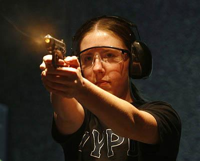 Crystal Perry, an employee of Salt Lake City's Impact Guns, fires a 9mm handgun on the store's indoor range. Firearms instructors are increasingly seeing women taking classes in gun safety and shooting skills.