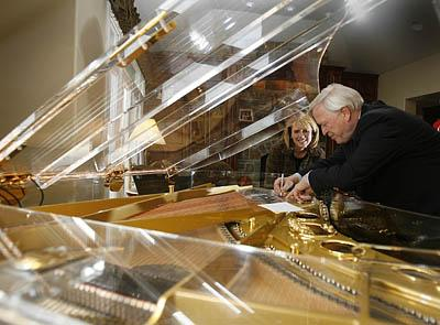Nikolaus Schimmel signs one of the rare glass pianos he crafted while its owner, Katie Warnock, of Bountiful, looks on. Warnock's piano is one of only five such instruments in the world designed with ebony and gold accents around the side.