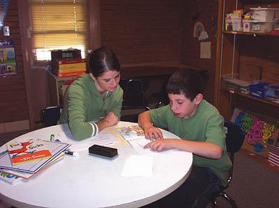 Katie Herem, a University of Utah graduate student in speech pathology, helps Derek Moya with his reading skills at the Neighborhood House in the Glendale area.
