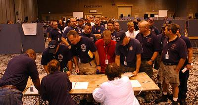 Firefighters line up Monday in Atlanta to give their names to FEMA personnel drawing up deployment lists. Many will be assigned to hand out fliers.