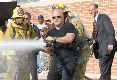 In this undated publicity photo released by FX Network, Michael Chicklis as Detective Vic Mackey operates a fire hose in the fifth season premiere of