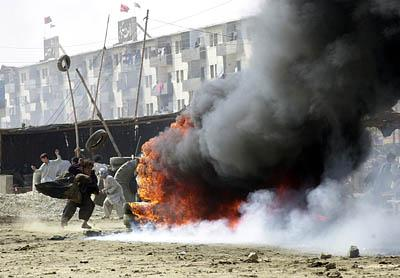 Angry Muslims, above, burn tires Friday in Karachi, Pakistan.