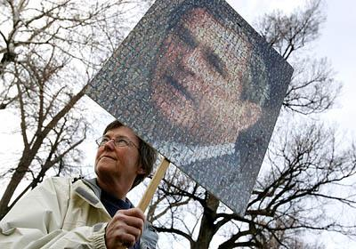 Gail Davis carries a poster of President Bush made up of 1,500 portraits of Armed Forces soldiers who have died during the Iraq war. Davis was one of about 200 anti-war protesters who marched from Pioneer Park to a rally on the steps of the City-County Building on Saturday.