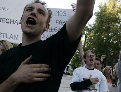 Demonstrators on Tuesday protest against Mexican President Vicente Fox and illegal immigration in front of the Governor's Mansion while Fox and Utah Gov. Jon Huntsman Jr. dine inside.  Brandt Barker, left, 20, of West Jordan, recites the Pledge of allegiance Tuesday in front of the Governor's Mansion during a Utah Minutemen rally.