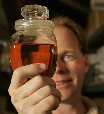 Graydon Blair displays a sample of biodiesel one of his clients made from waste vegetable oil. Blair, who is trying to mediate the escalating grease war, sells biodiesel-brewing equipment from a shop at his home.