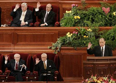 President Thomas S. Monson (right), along with (clockwise from Monson) President James E. Faust, President Gordon B. Hinckley, Presiding Bishop H. David Burton, and Keith McMullin (Burton's second counselor), raise their hands to sustain the general authorities of the church. LDS General Conference Saturday AM session, Conference Center, Salt Lake City.