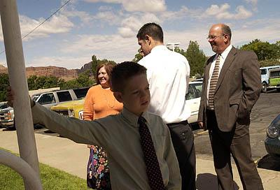 Restless while waiting for his family (including father David Knutson; far right) to join him inside for Sacrament Meeting, 8-year-old Reyce Knutson swings on the railing outside their LDS chapel in Moab.