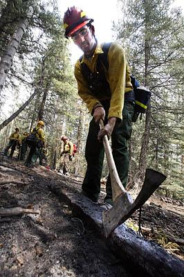 Ben Feiro, who is a member of a fire fighting team from Northern Minnesota checks for hot spots along a fire line  in the Kaibab Forest's