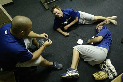 Jason Mooneyham, left, relaxes in the clubhouse with teammates Russ Mitchell, right, and Adam Goodwin before a recent game. Mooneyham makes $1,100 a month.
