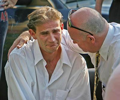 An emotional father of missing five-year-old girl Destiny Norton, Rick Norton (left), is comforted by a his boss Bart Hill outside his home  July 17, 2006 after Destiny was listed on an Amber Alert after going missing from her Salt Lake City home.