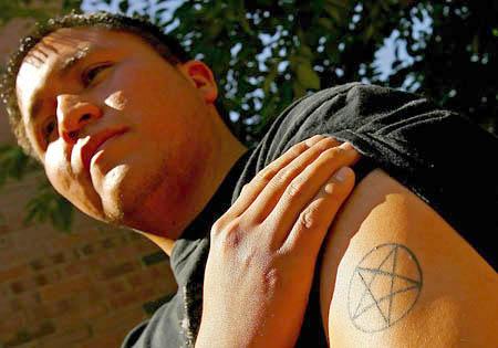 Panelist Michael Negale displays his tattoo before speaking at Sunstone.