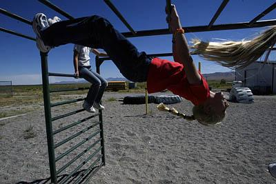 Fifth-grader Lizzy Allred, center, plays on the monkey bars during recess at West Desert Elementary/High School.