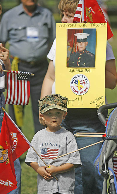 Four-year-old Kolby Jensen stands at attention during the playing of the Marine Corp Hymn. His mother Kim Jensen of North Salt Lake holds a picture of Kolby's older brother Whit Bell, who is in Iraq. The two were at the rally to support the troops at Liberty Park in Salt Lake City.  <a href=