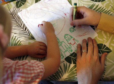 Coloring with dad, Sophie Christensen and her father Ben draw out the members of the family on the kitchen table Wednesday afternoon.