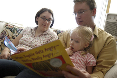 Jessie and Ben Christensen read a story with their daughter, Sophie, 3, in their Orem home. Below, Sophie and Ben work together on a picture of their family. The Christensens, who also have a 2-month-old son, acknowledge it can be a struggle to reconcile their LDS faith and their marriage with Ben's homosexuality. They have shared their experiences with other mixed-orientation Mormon couples.