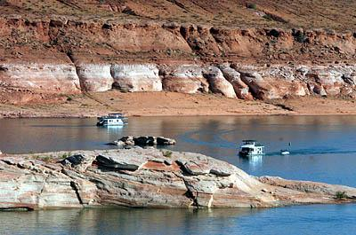 Boaters are dwarfed by the sandstone walls of Lake Powell, which holds Colorado River water. The lighter colors on the shore show how the water level has fallen. Global warming may affect the way Utah, Wyoming, Colorado, New Mexico, Nevada, Arizona and California share Colorado River water, researchers say.