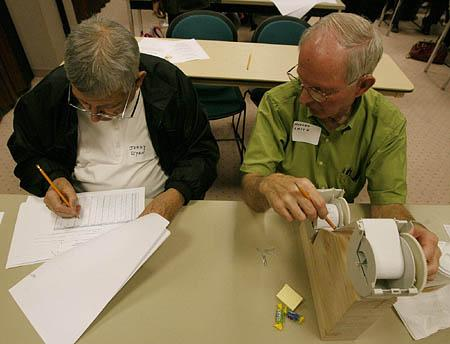 Jerry Ryan and Morgan Smith check the paper receipts against the electronic tally. The paper backups in 1 percent of the Utah's 7,500 voting machines will be hand-counted.