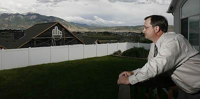 From his backyard deck, Stan Torgersen looks out Tuesday at a vent covering put up by a neighbor with whom he's having a dispute. The neighbor, Darren Wood, describes the covering as decorative