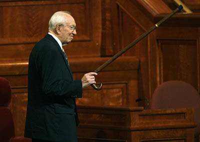 LDS President Gordon B. Hinckley salutes with his cane at the Conference Center as he leaves the morning session Saturday.