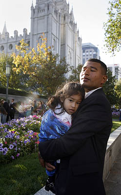 Jose Contreras holds his sleepy 2-year-old daughter, Kate, as they wait to enter the Conference Center on Saturday morning.