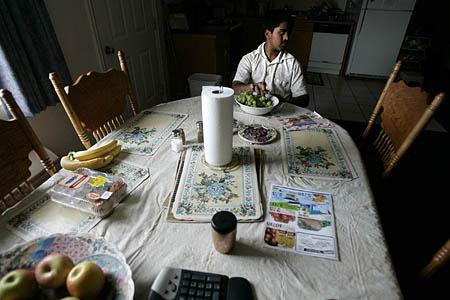 Kunal Sah, 13, watches TV from the dinner table in the apartment he shares with his uncle in the Ramada Limited hotel in Green River.