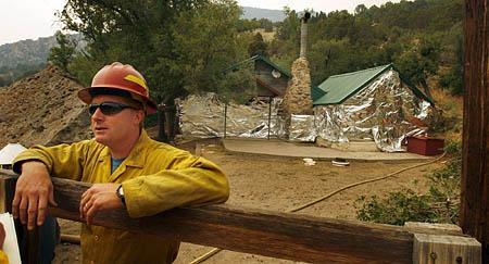 Mike Martin, from the Chippewa National Forest Service, stands at a cabin that has been covered in cabin wrap for protection in the Mineral Mountains outside of Milford.