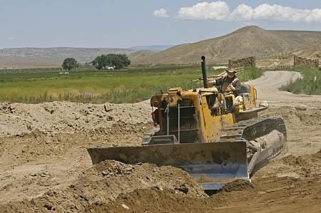 Brother Joseph Marie operates a bulldozer, leveling the land where the monks are building a larger home.