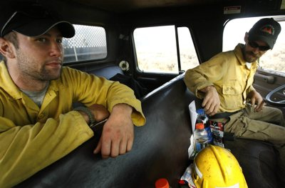 Eric Moore, left, a Marine reservist with the Amarillo, Texas, and Sean Erskine with Spanish Fork's Intermountain Fire Service head towards the electric powerline road to create a large fire break in case the shifting afternoon winds blow the fire towards Fountain Green.