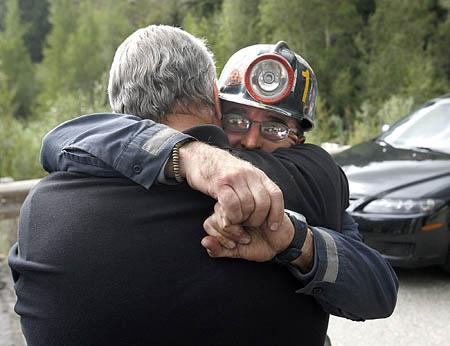 Bodee Allred, the Crandall Canyon mine safety director, right, hugs Emery County Sheriff Lamar Guymon on Wednesday at the mine command center.