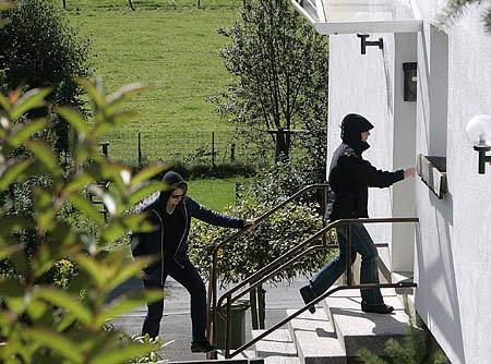 Police officers enter a holiday home, in which three terrorist suspects were arrested, in the village of Medebach- Oberschledorn, western Germany, on Wednesday.