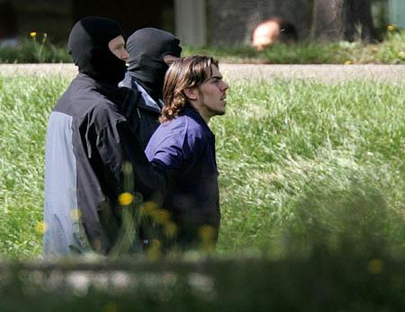 A man believed to be a terror suspect is led away by masked police at the federal court in Karlsruhe, southern Germany, on Wednesday.