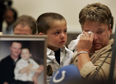 Sheila Phillips, mother of miner Brandon Phillips who was killed in the Crandall Canyon mine in Utah, wipes away a tear as her grandson, Gage Phillips, 5, looks on during a House Education and Labor Committee hearing on mine safety on Capitol Hill, Wednesday. In the foreground is a photo of Brandon Phillips and his son, Gage.