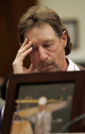 Steve Allred, brother of miner Kerry Allred who was killed in the Crandall Canyon mine in Utah, pauses during his testimony before the House Education and Labor Committee hearing on mine safety on Capitol Hill, Wednesday, Oct. 3, 2007. In the foreground is a photo of Kerry Allred.
