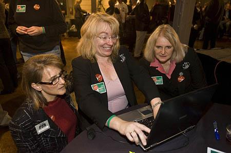 Cheryl Phipps, state PTA legislative vice president, is flanked by PTA Education Commissioner Holly Langton, left, and President Marilyn Simister as she checks statewide results of the school voucher proposition.