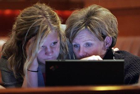 Ashley Holmes and her mother Erin Holmes watch the poll numbers on a laptop as the pro-voucher camp's referendum one fails Tuesday night. The two are the daughter and wife of Doug Holmes, who is the co-chair of Parents for Choice in Education.