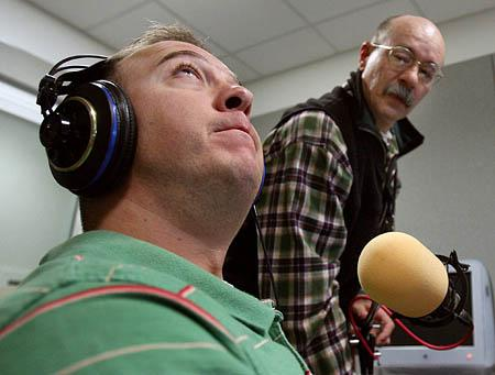 Lee Kelley, left, gets comfortable as KUER technician Lewis Downey adjusts a microphone at the radio station's studios in Salt Lake City. Kelley is back from serving in Iraq and is hoping to begin a new career as a writer.