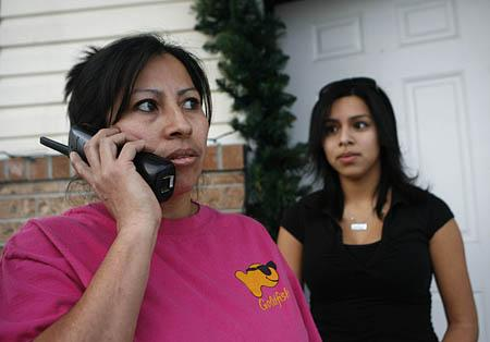 Gloria Alvanes, 37, of Logan, is joined by her daughter, Marilyn Cornejo, right, as she takes a phone call Tuesday from a worried member of the Latino community. Alvanes's husband, Ramiro Vieyra, was one of those taken by federal agents from Swift & Co. meat-packing plant in Hyrum.