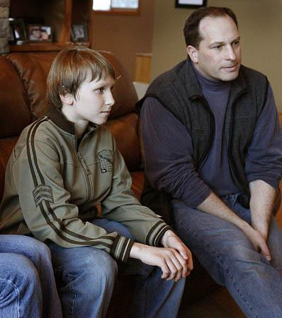 Eleven-year-old Max Zilvitis sits on the sofa next to his father, Brian Zilvitis, on Thursday and recalls a scary experience of being caught in an avalanche near Park City on Sunday.