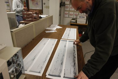 Seismologist Relu Burlacu looks over the seismic activity from Wells, Nev., on a Helicorder print out at the University of Utah's seismic station.