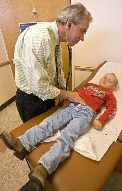 Midtown Community Health Center Medical Director Dr. Richard Gregoire examines Tate Johnston, 3, who came to the Ogden clinic with a cough.